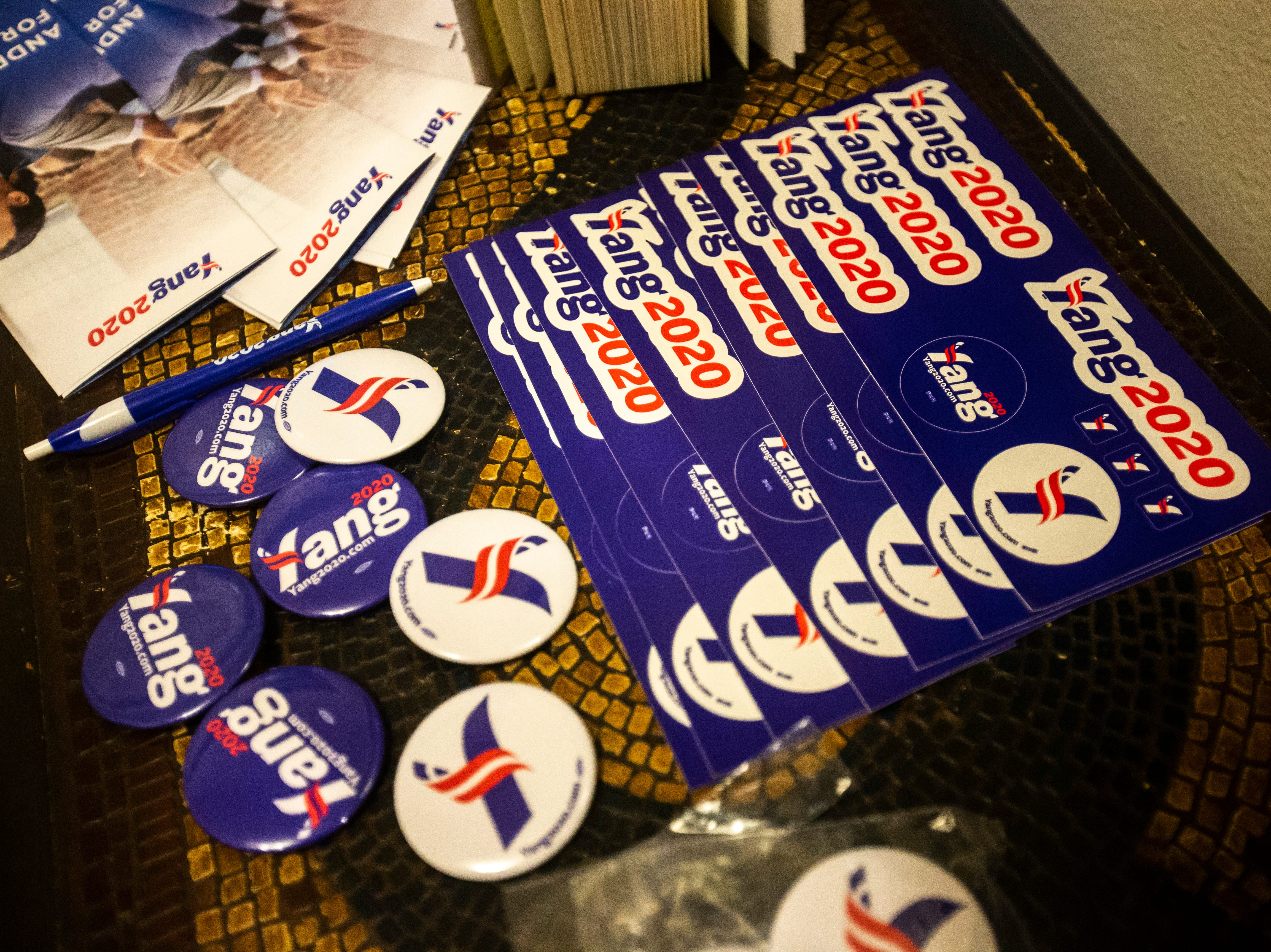 """Stickers and buttons for Andrew Yang, a 2020 Democratic presidential candidate, sit on a table at the """"Potluck Insurgency,"""" a dinner party organized by local activists, on Sunday, March 10, 2019, at a home in Iowa City, Iowa."""