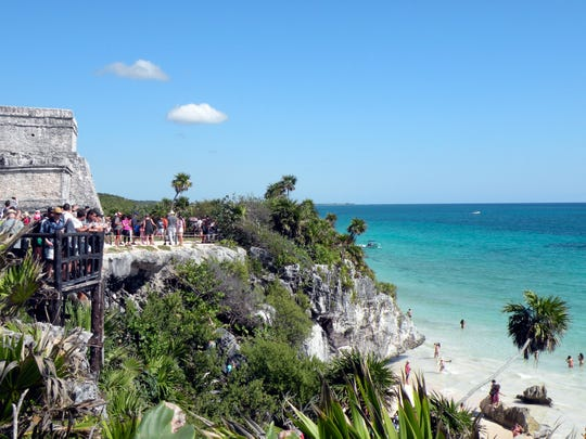 At Tulum's archaeological site, the Caribbean Sea's turquoise waters and white sand complement the beauty of the Mayan ruins.