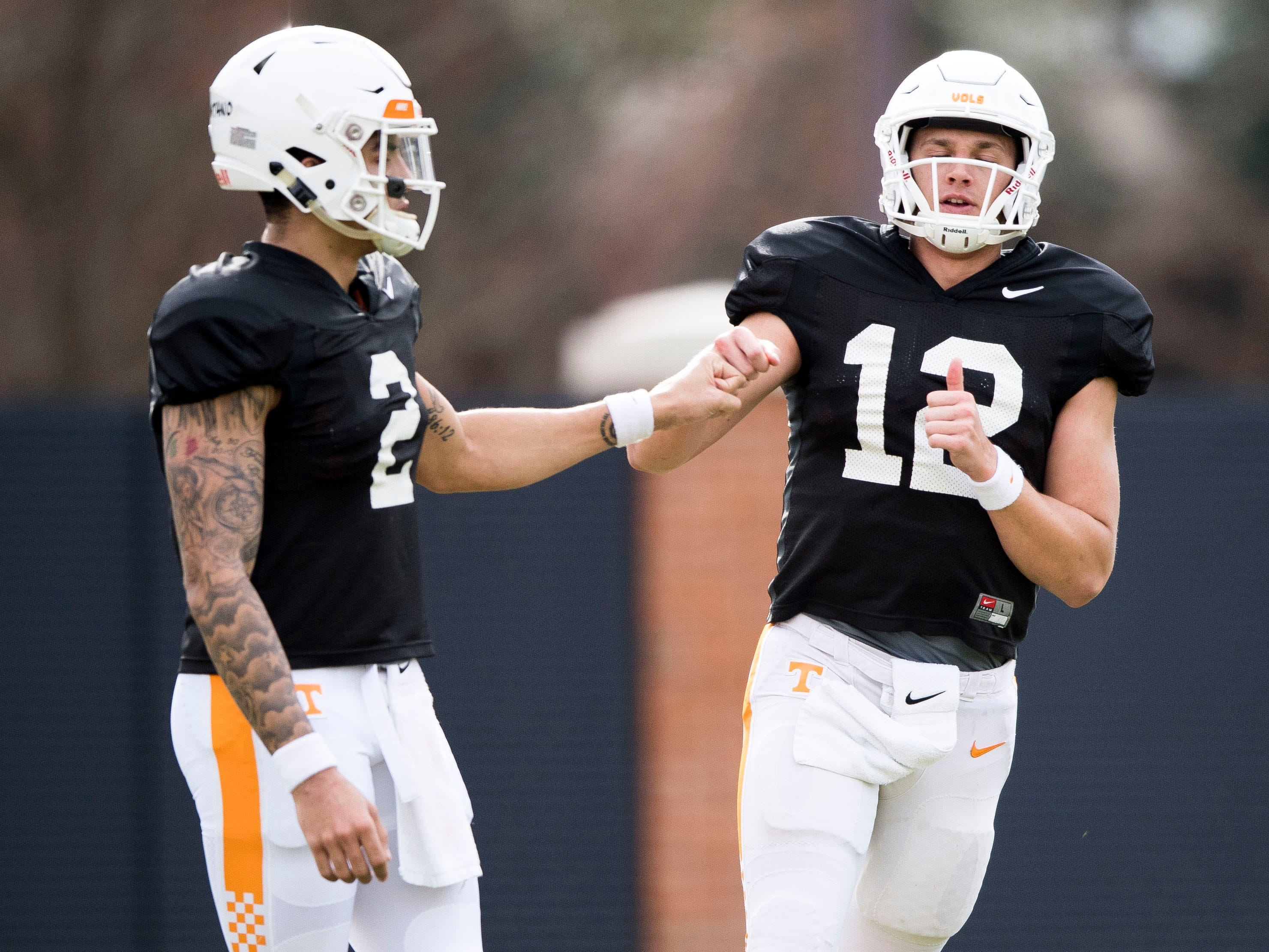 Tennessee quarterback Jarrett Guarantano (2) bumps fists with quarterback JT Shrout (12) during Tennessee's afternoon football practice on Monday, March 11, 2019.