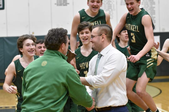 Howell basketball players celebrate as coach Nick Simon is presented the regional championship trophy on Thursday, March 7, 2019.