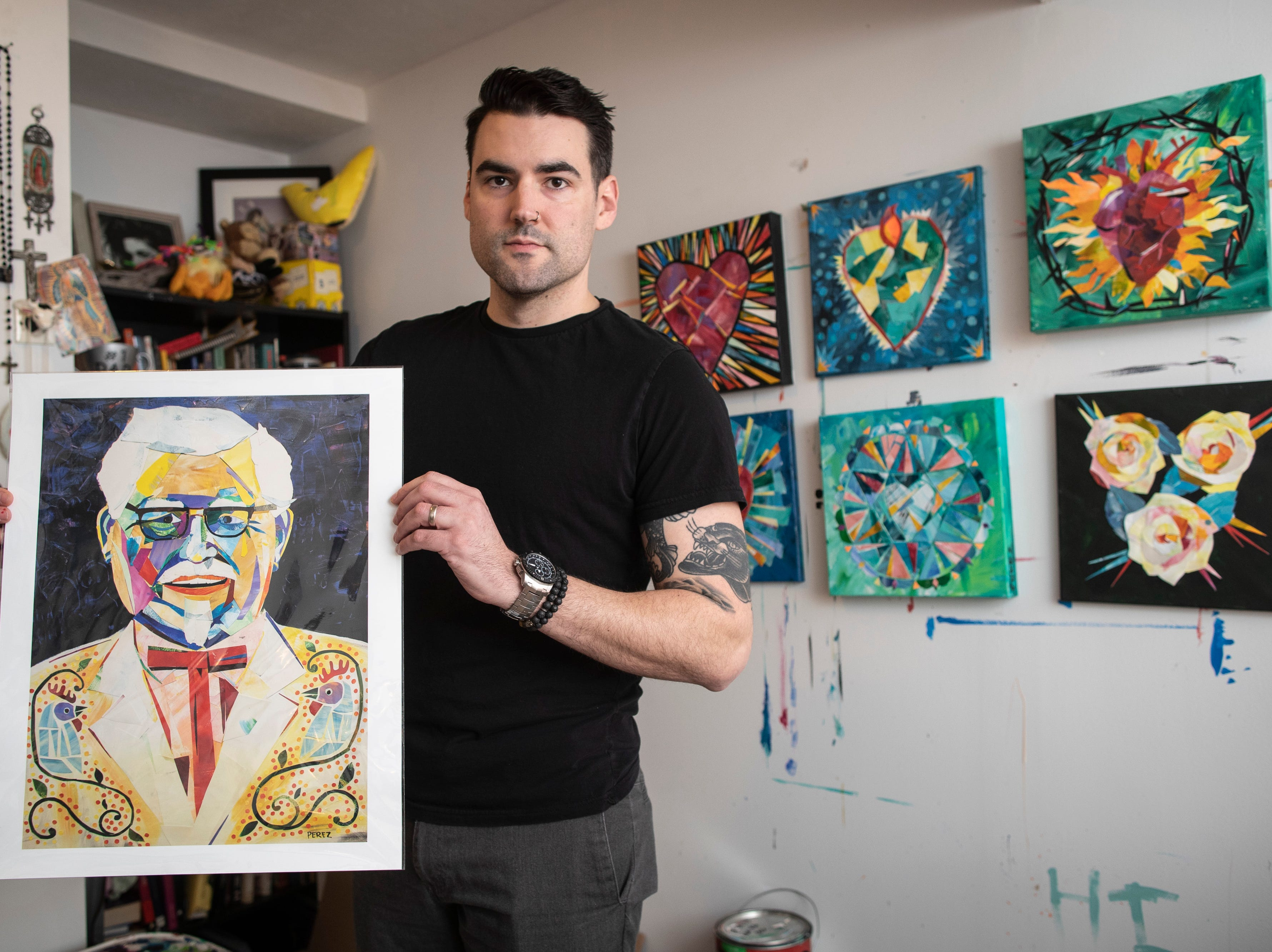 """Louisville artist Andy Perez holds a print of his colorful painted collage portrait of Kentucky Fried Chicken founder Colonel Sanders in his home studio. The artwork was recently featured in a french KFC commercial. """"I was interested in the colonel because of the story of his perseverence,"""" Perez said. """"He was told no so many times and now it's one of the most famous chicken recipes in the world."""" March 11, 2019"""