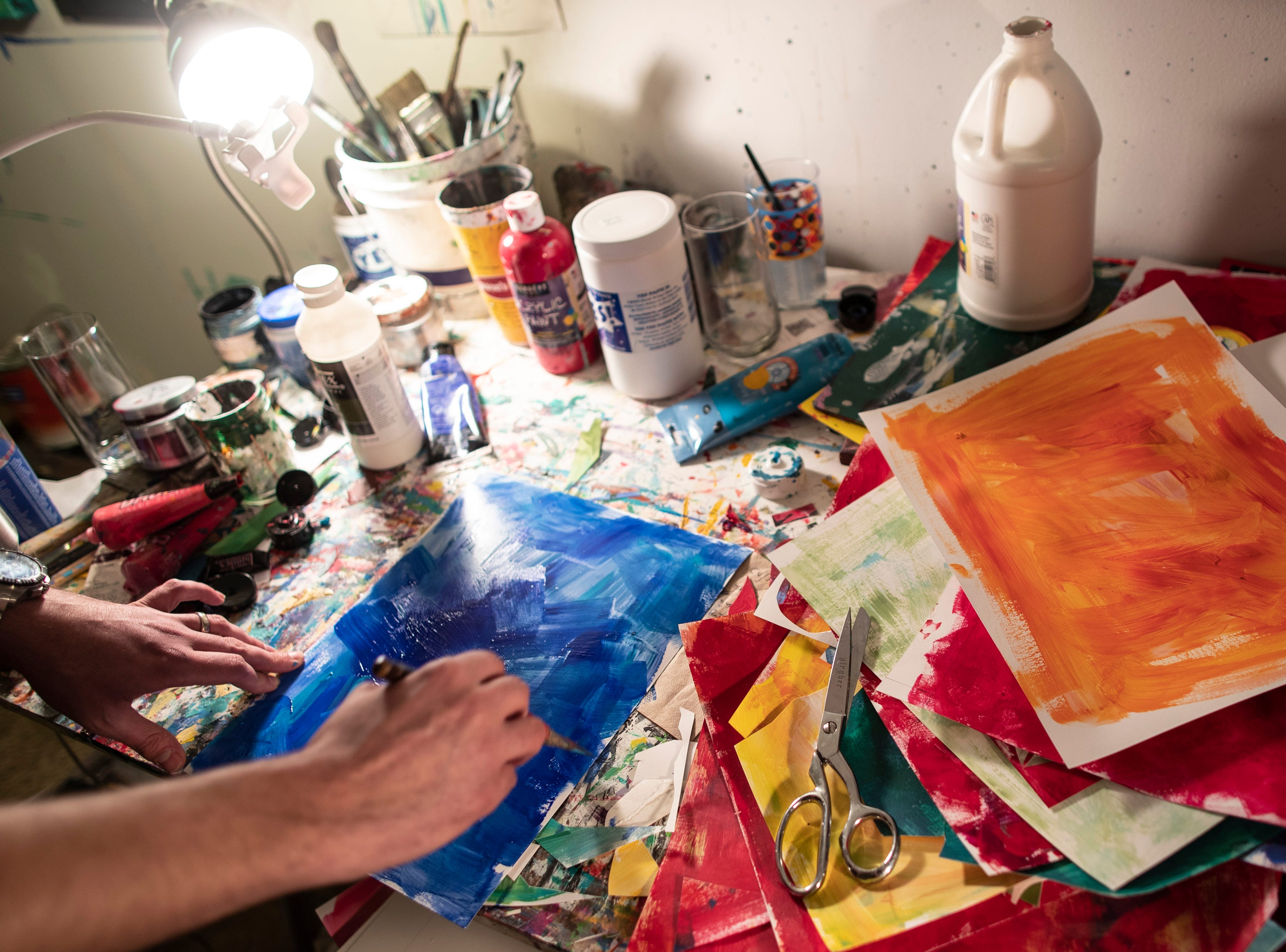 Louisville artist Andy Perez works on painting collage pieces in his home studio. March 11, 2019