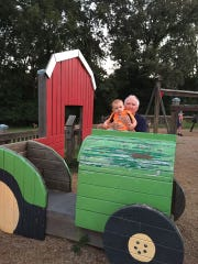 Jack Cooper holds Ben Griffin while enjoying the Playground of Dreams several years ago. The playground was demolished last week.