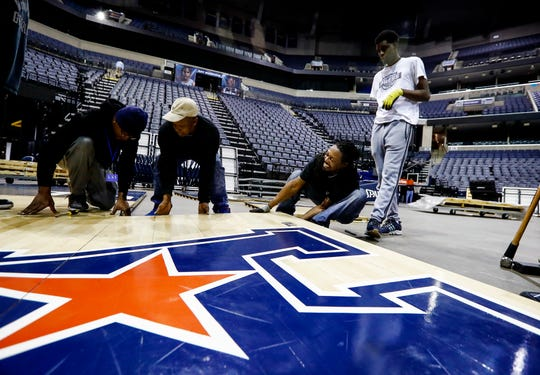 FedExFourm court conversion crew assembles the American Athletic Conference Basketball court for the upcoming tournament games this week.