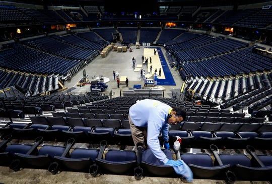 Charlie Thornton cleans arena seats as the FedExFourm court conversion crew assembles the American Athletic Conference Basketball court for the upcoming tournament games this week.