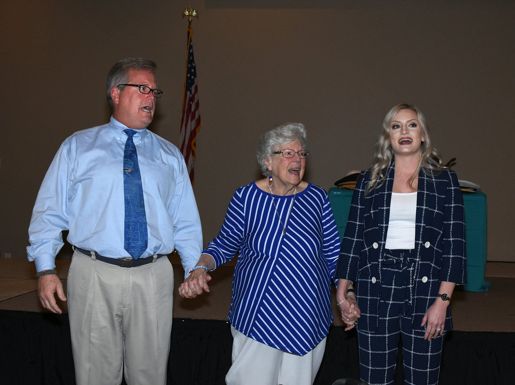"Herb Jr., Emily Savage and granddaughter Alix Guillotte lead the singing of ""God Bless America."" The life of iconic island architect Herb Savage was celebrated in a ceremony Sunday afternoon at the Rose History Auditorium, with military honors and reminisces from family and friends."