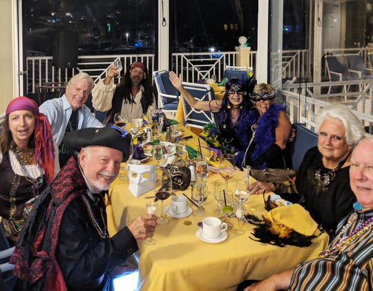 """Yacht Club Mardi Gras partygoers enjoyed a Louisiana cuisine of shrimp, red beans and rice, brisket and a traditional New Orleans """"King Cake.""""  From left,  Henry Stanley, Linda Marr, Jim McKeown, Jim Marr, Lauri Kalanges, Mary McKeown, Sandy and Bill Wallen"""