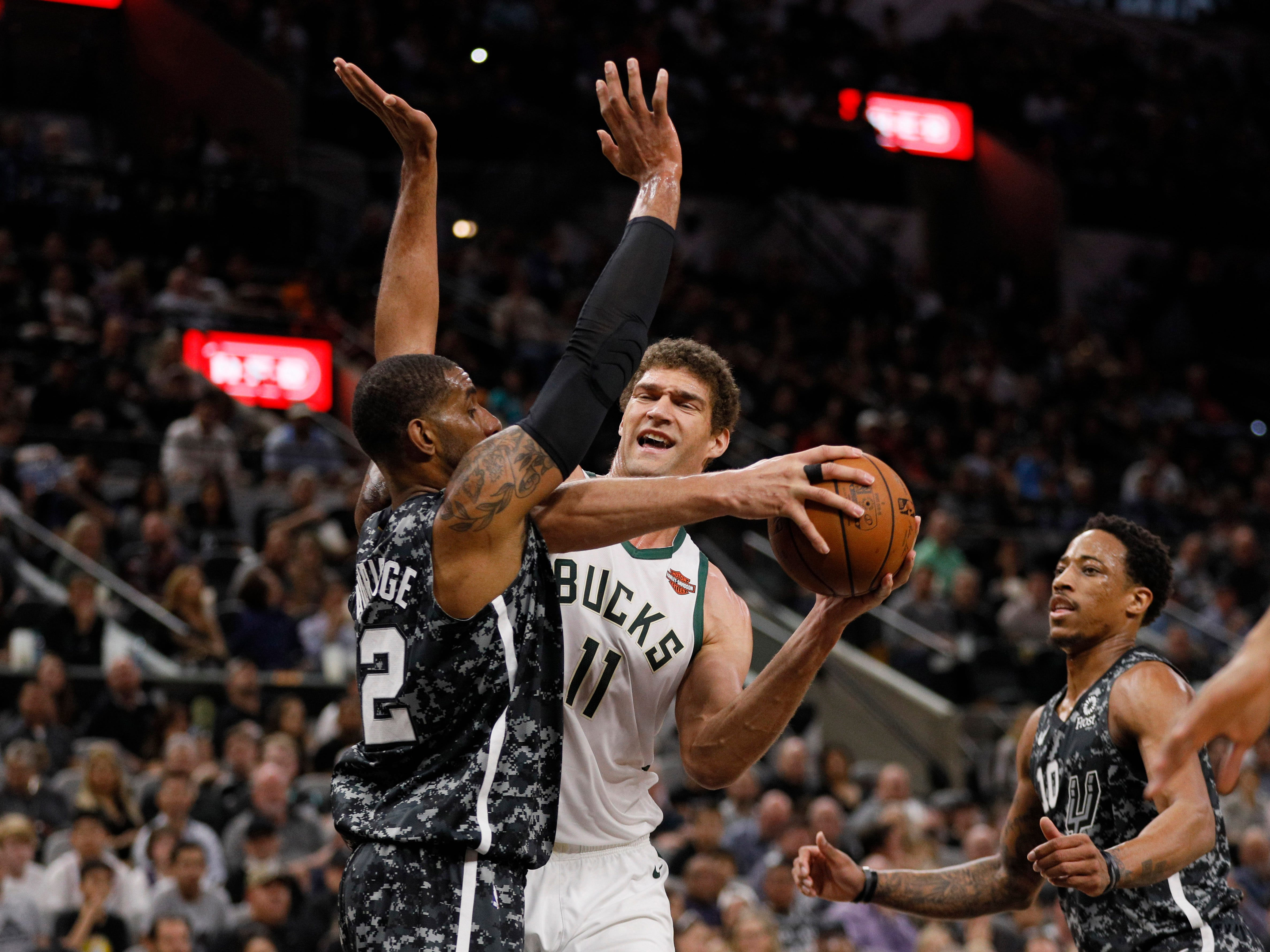 Bucks center Brook Lopez tries to power past Spurs forward LaMarcus Aldridge on his way to the basket Sunday.