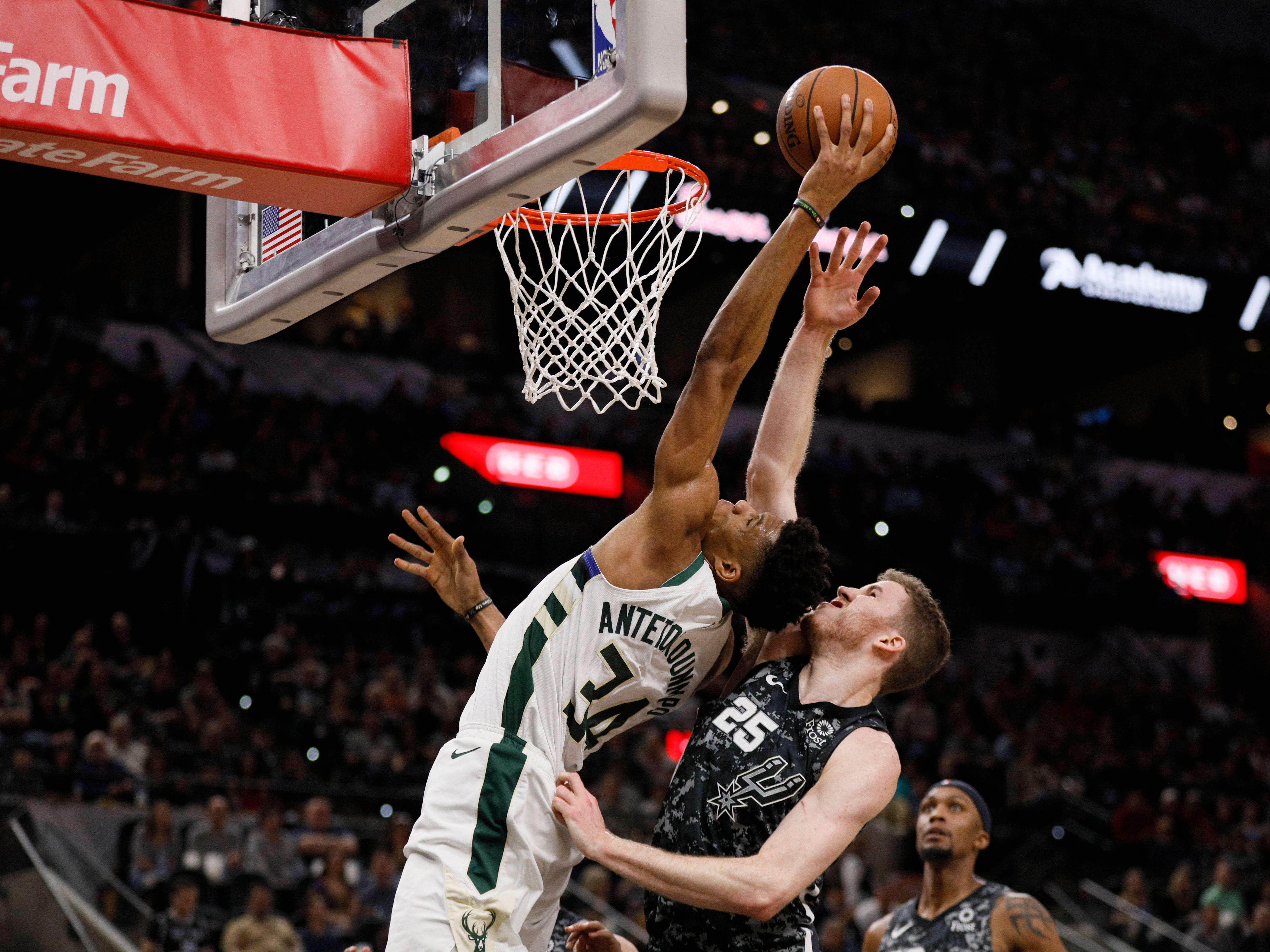 Bucks forward Giannis Antetokounmpo goes up for a dunk against Spurs center Jakob Poeltl during the first half.
