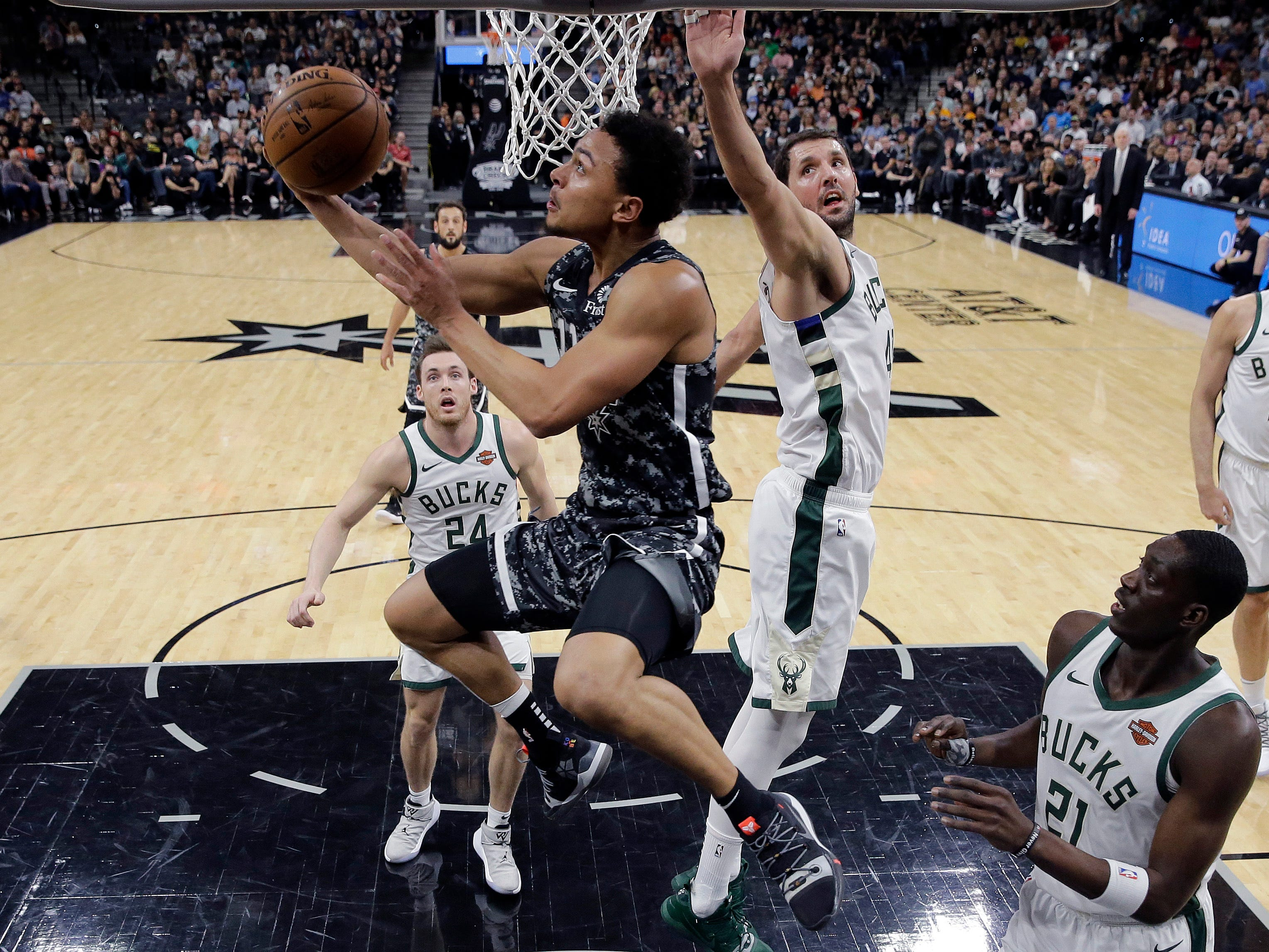 Spurs guard Bryn Forbes goes past Bucks forward Nikola Mirotic and duck under the basket as he goes up for a shot during the first half.