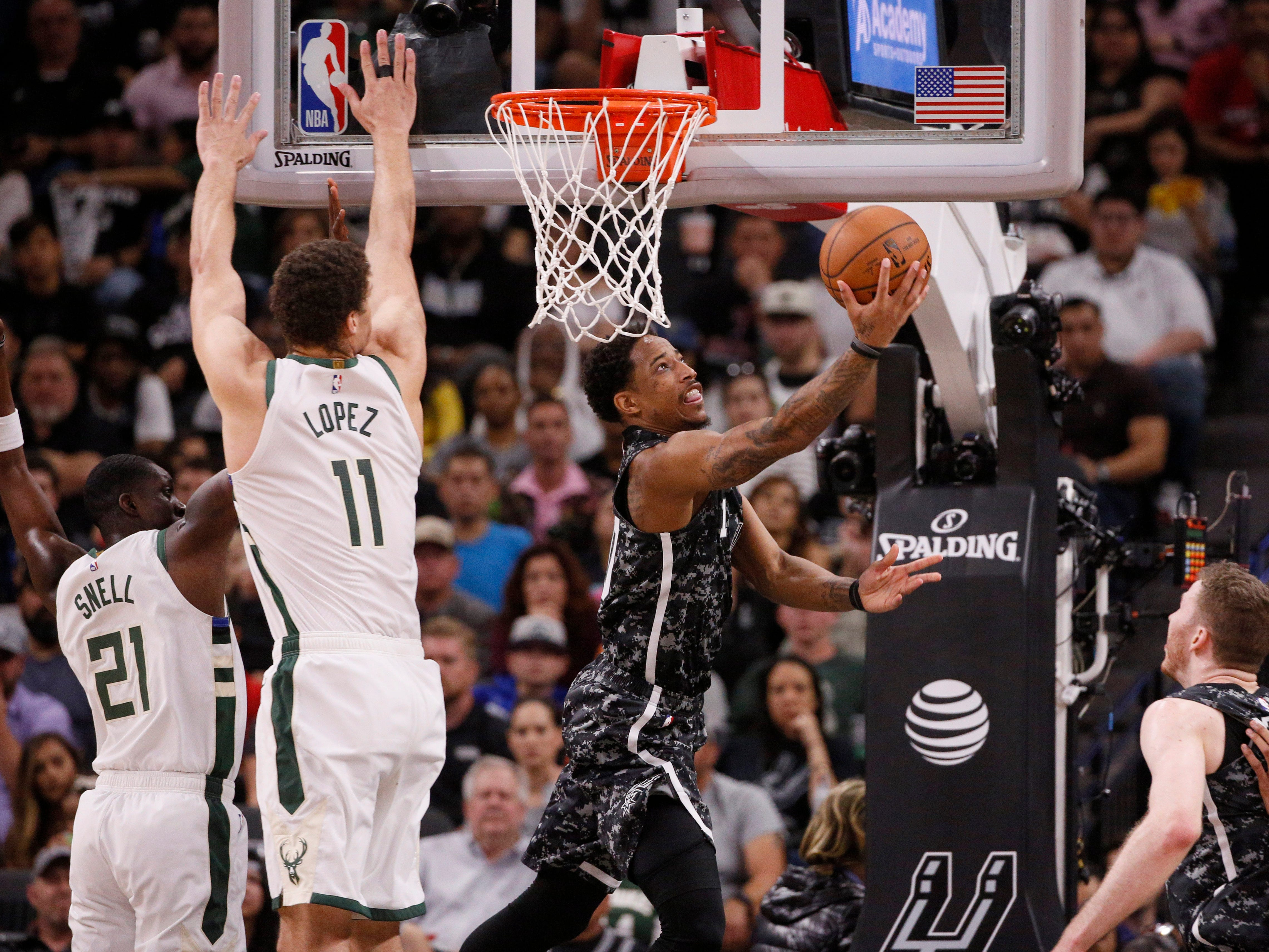 Spurs guard DeMar DeRozan gets past Tony Snell and Brook Lopez of the Bucks for a reverse layup on Sunday.