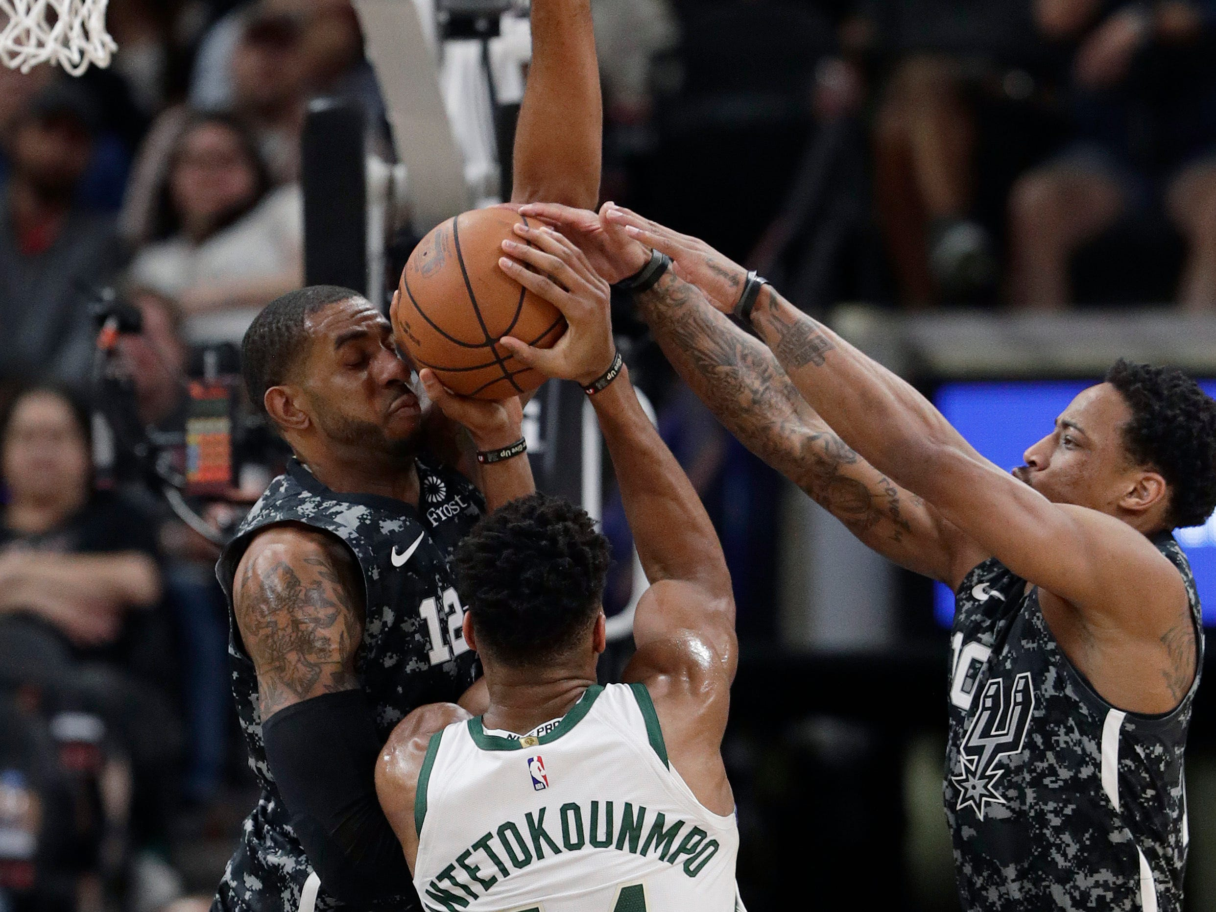 Bucks forward Giannis Antetokounmpo finds the sledding tough as he tries to put on a shot between the Spurs' LaMarcus Aldridge (left) and DeMar DeRozan on Sunday night.