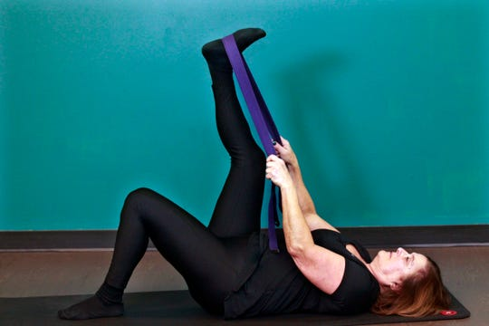 Barbara Cohn demonstrates the  hamstring stretch strap exercise.