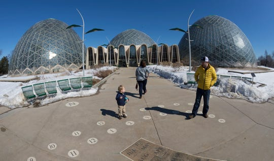 People are shown outside the Mitchell Park Domes on Monday in Milwaukee. A report has recommended tearing down the domes and replacing them.
