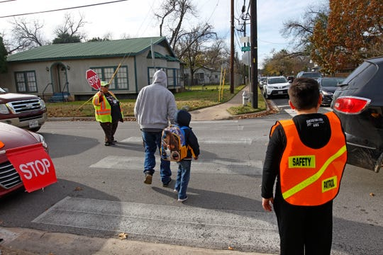 A crossing guard (left) and a student safety patrol member help others cross  the street at Govalle Elementary School in  Austin, Texas.