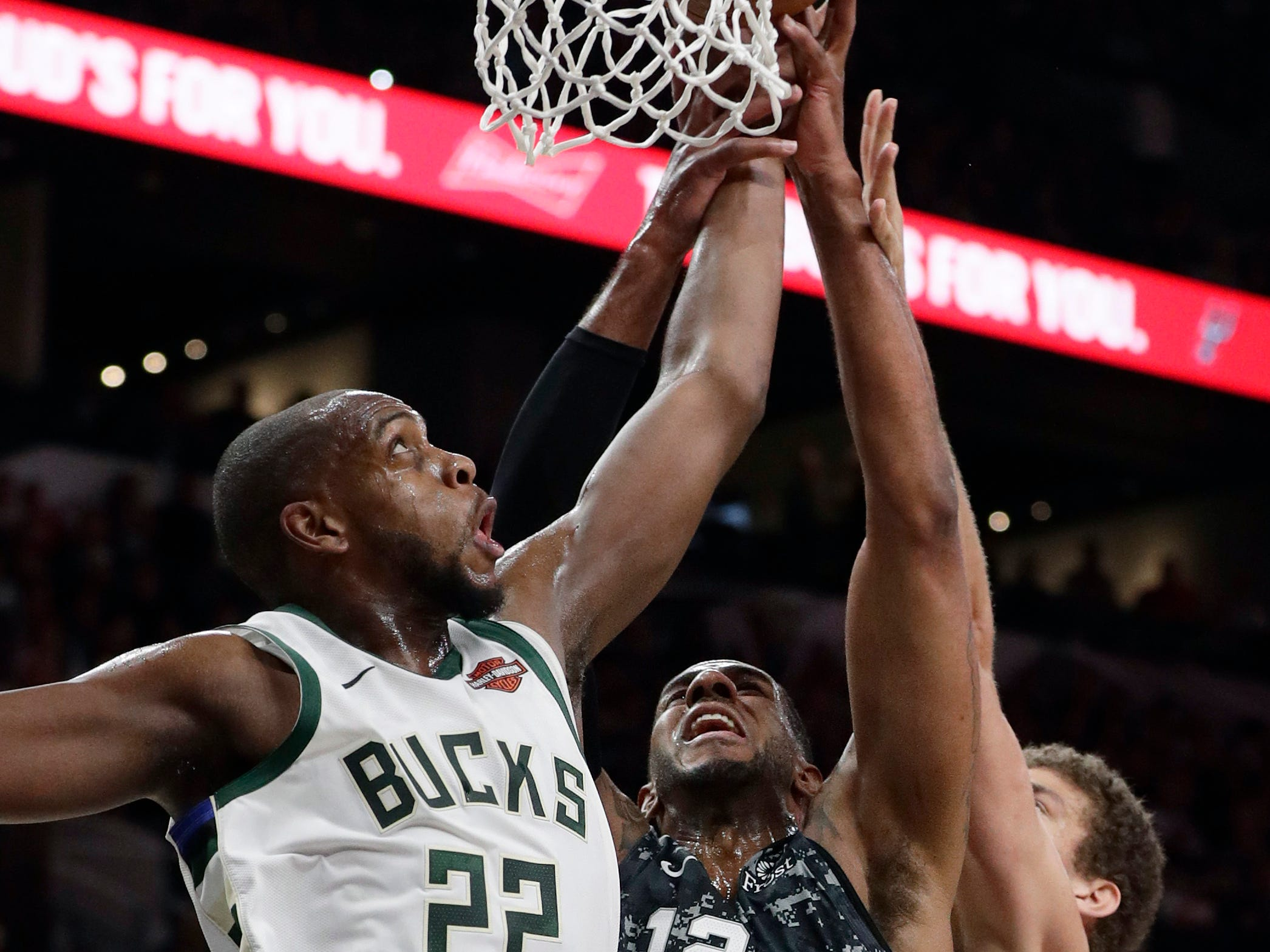 Spurs center LaMarcus Aldridge battles Bucks forward Khris Middleton (22) and center Brook Lopez for a rebounds during the first half.