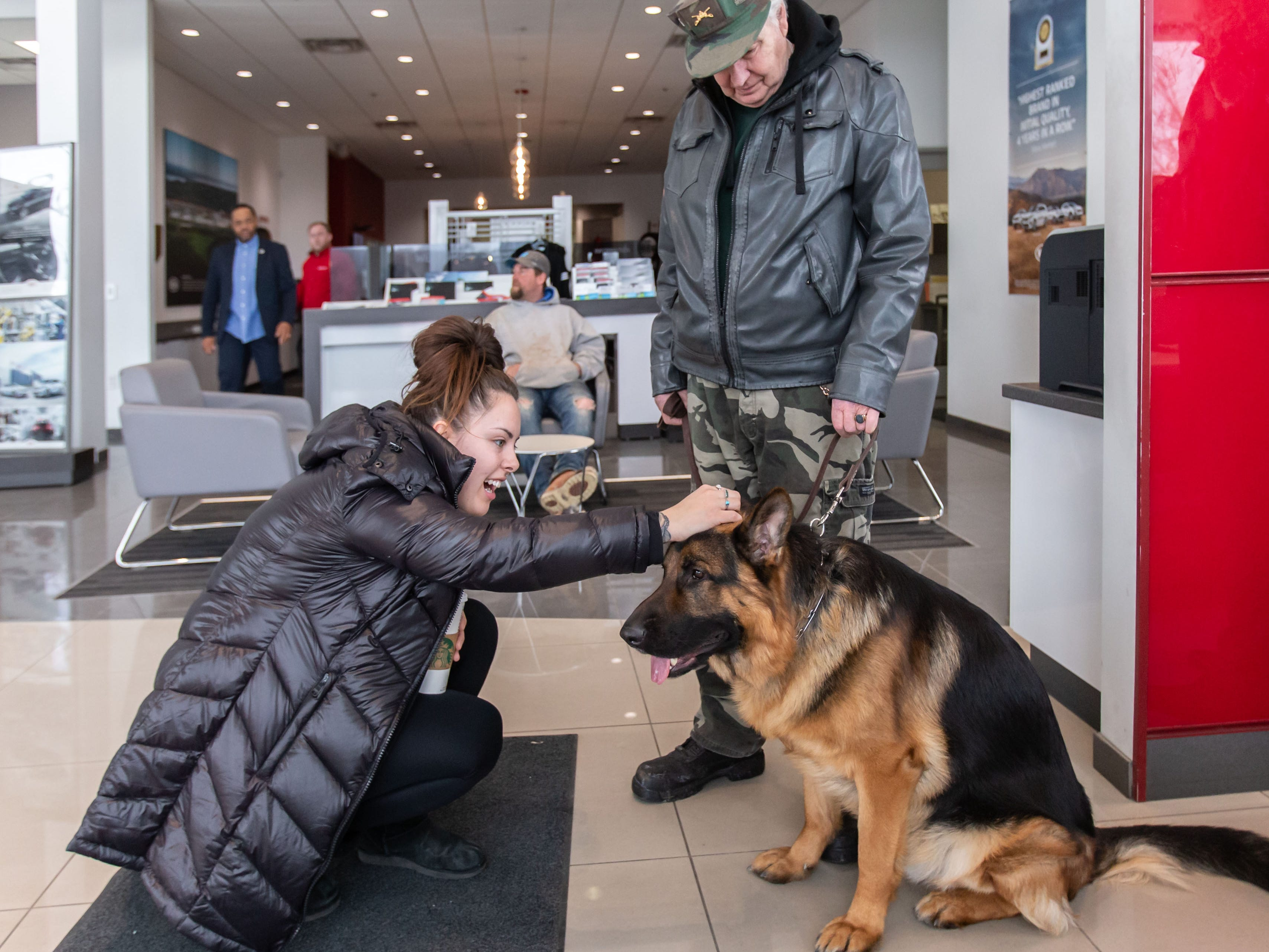 Ashley Lemay of Milwaukee pets Grizz, a purebred German Shepherd owned by Dennis Kratz of Grafton, during the Adopt a Pet program at Russ Darrow Kia of Wauwatosa on Saturday, March 9, 2019. The event, held in partnership with the Humane Animal Welfare Society (HAWS) in Waukesha and the German Shepard Dogs Club of Wisconsin (GSDCW), offered attendees the opportunity to meet and adopt dogs, cats, rabbits, and other types of animals.