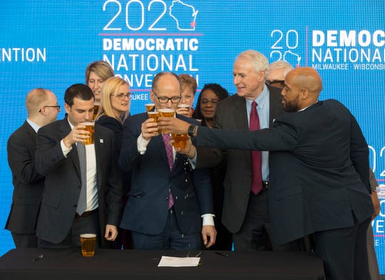 Democratic National Committee Chairman Tom Perez (center) reacts after spilling a celebratory beer on the convention contract with Milwaukee Bucks Senior Vice President Alex Lasry (left), Milwaukee Mayor Tom Barrett and Lt.  Gov. Mandela Barnes following the official announcement that Milwaukee will host the 2020 Democratic National Convention at Fiserv Forum on Monday. Milwaukee snagged the event over Houston and Miami.