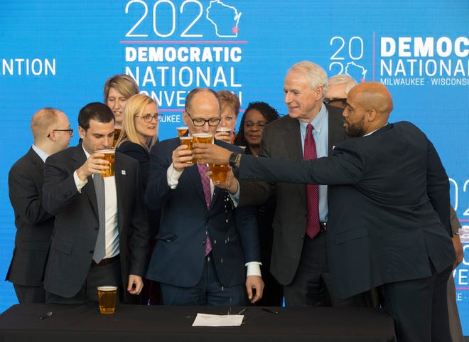 Democratic National Committee Chairman Tom Perez (center) reacts after spilling a celebratory beer on the convention contract with Milwaukee Bucks Senior Vice President Alex Lasry (left), Milwaukee Mayor Tom Barrett and Lt. Gov. Mandela Barnes following the official announcement in March that Milwaukee will host the 2020 Democratic National Convention at Fiserv Forum.