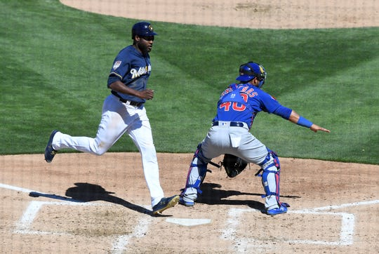 PHOENIX, ARIZONA - MARCH 10: Lorenzo Cain #6 of the Milwaukee Brewers scores on a double by Yasmani Grandal #10 during the third inning of a spring training game as Willson Contreras #40 of the Chicago Cubs waits for the throw from right field at Maryvale Baseball Park on March 10, 2019 in Phoenix, Arizona. (Photo by Norm Hall/Getty Images)