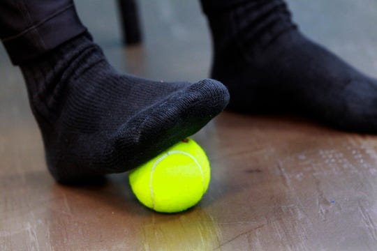 Barbara Cohn demonstrates the tennis ball foot stretch.