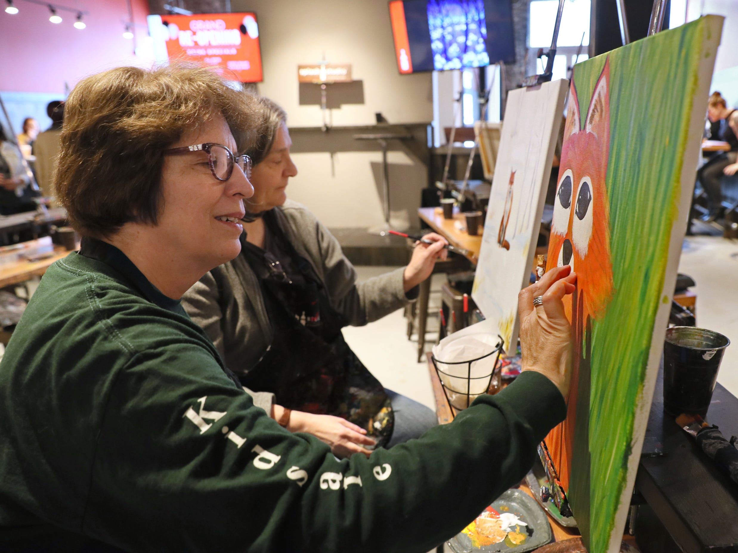 Terri Torbeck of Brookfield (foreground) and her friend, Gillian Simpson (rear) of Fox Point, paint pictures of foxes. Splash Studio moved from the Third Ward to 1815 E. Kenilworth Place on the east side of Milwaukee.  On Sunday, they held a grand reopening event.