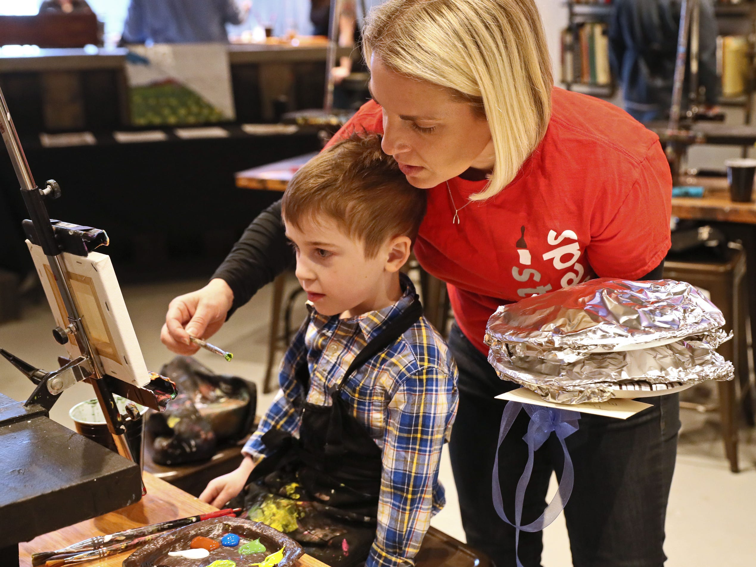 Marla Poytinger, who along with husband David owns the business, helps her son, Micah Poytinger, 5, get set to do some painting. Splash Studio moved from the Third Ward to 1815 E. Kenilworth Place on the east side of Milwaukee.  On Sunday, they held a grand reopening event.