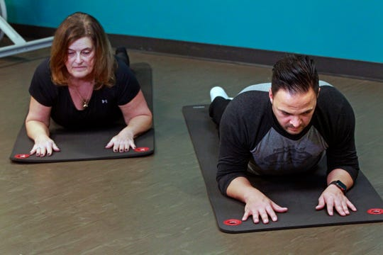 Barbara Cohn, left and  Ryan Poolay  demonstrates a segment of the yoga flow sequence stretch exercise.