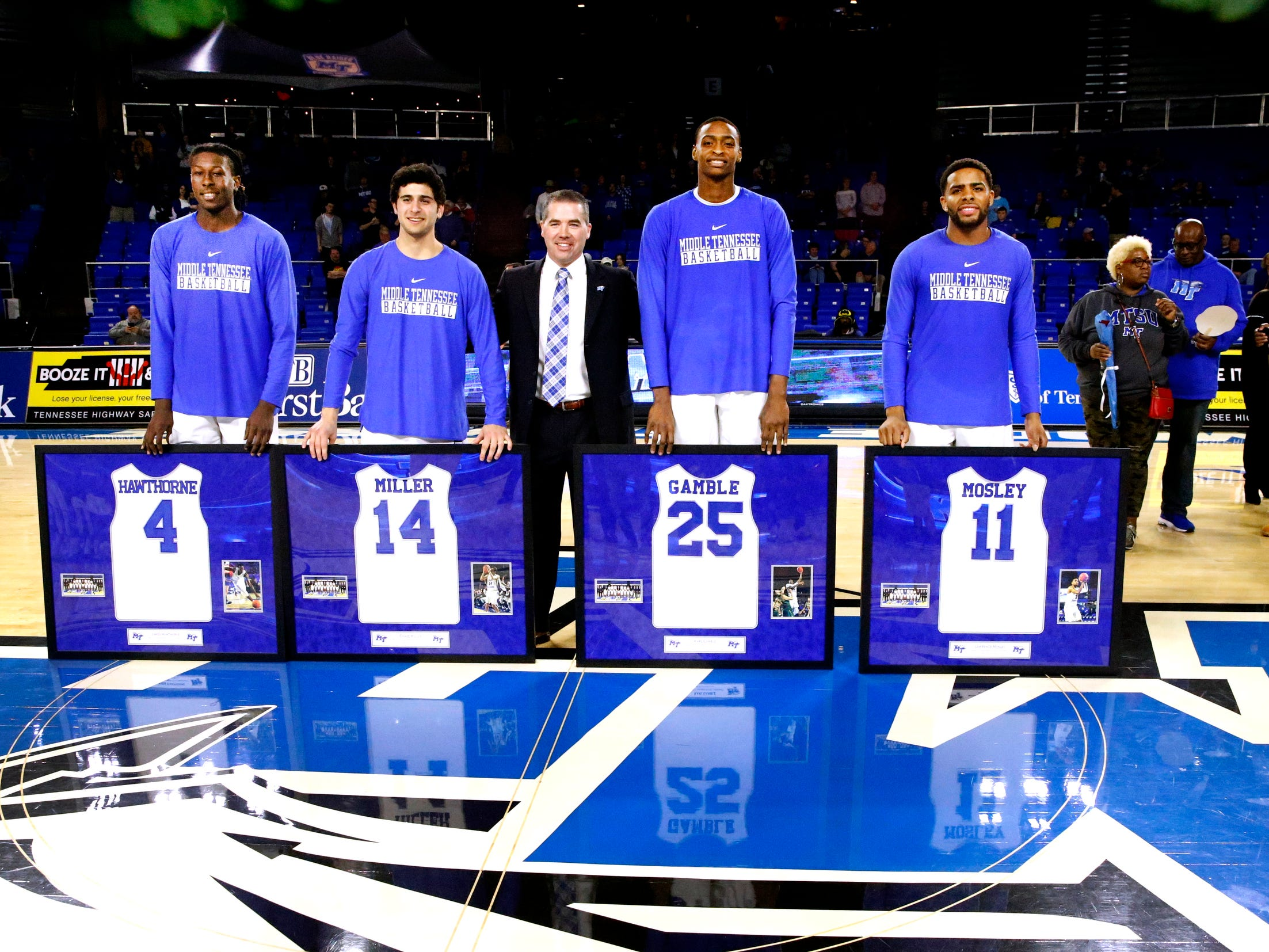 (L to R) MTSU senior forward James Hawthorne (4), MTSU senior guard Chase Miller (14), MTSU head coach Nick McDevitt, MTSU senior forward Karl Gamble (25) and MTSU senior guard Lawrence Mosley (11) all stand on the center of the court as MTSU seniors were honored before the game against UTEP on Saturday, March 9, 2019, at Murphy Center in Murfreesboro, Tenn.