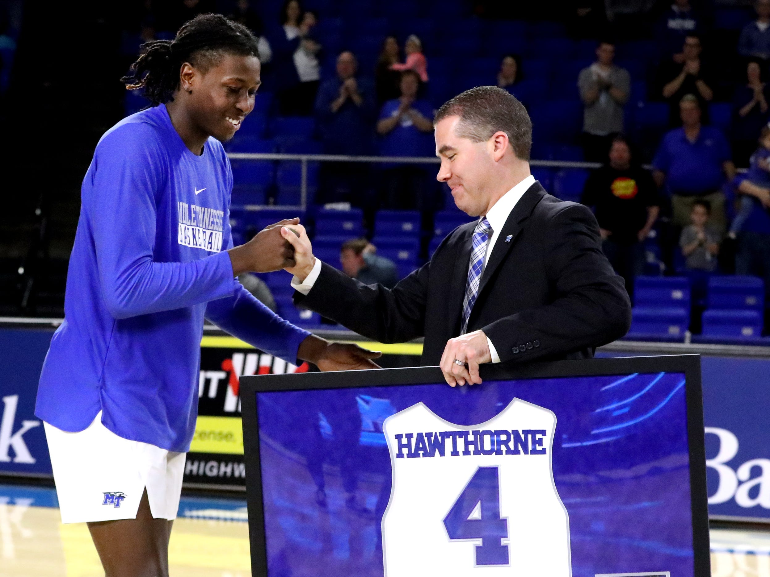 MTSU head coach Nick McDevitt honors MTSU forward James Hawthorne (4) with a framed jersey during MTSU's senior night before the game against UTEP on Saturday, March 9, 2019, at Murphy Center in Murfreesboro, Tenn.