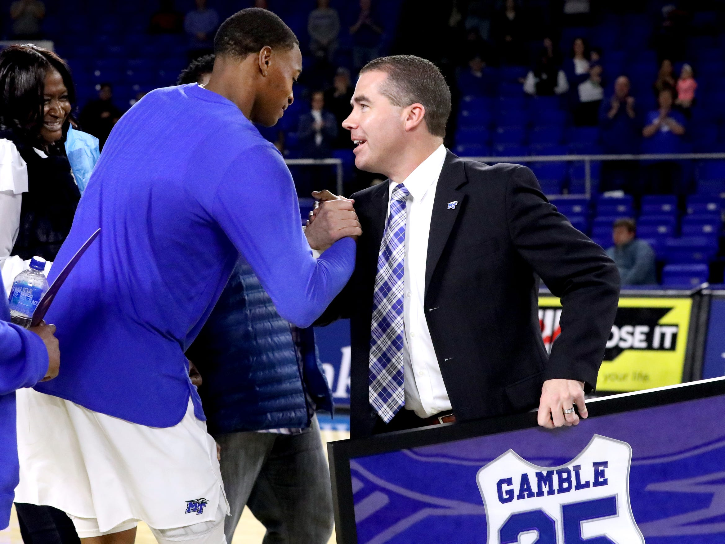 MTSU head coach Nick McDevitt honors MTSU senior forward Karl Gamble (25) with a framed jersey during MTSU's senior night before the game against UTEP on Saturday, March 9, 2019, at Murphy Center in Murfreesboro, Tenn.