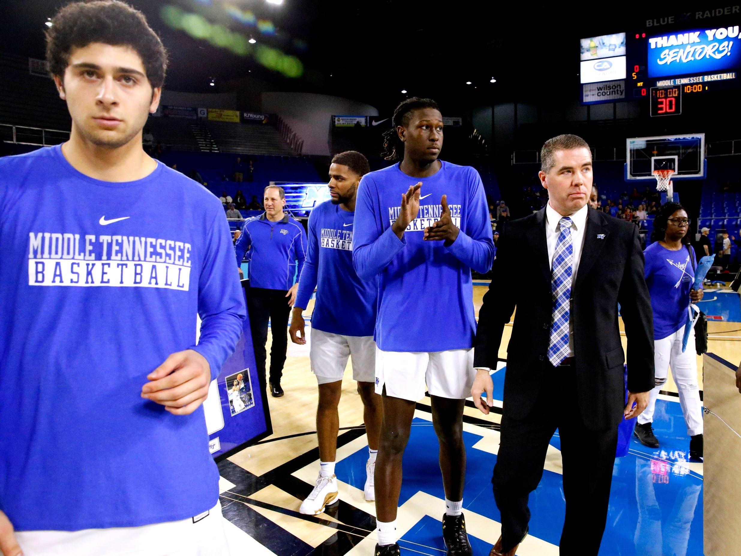 MTSU head coach Nick McDevitt heads off the court with senior players after they were honored before the game against UTEP on Saturday, March 9, 2019, at Murphy Center in Murfreesboro, Tenn.