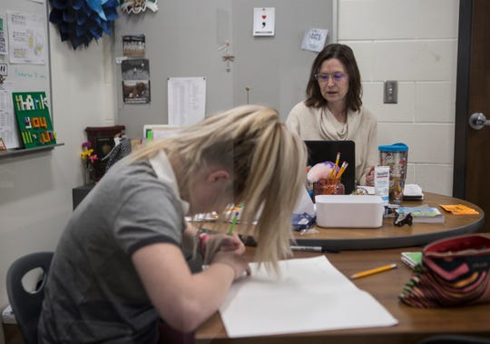 Shannon Cox, Johnstown's In-School-Support teacher, works at her desk as freshman Never Lash works on an art project. Cox started off as an In-School-Suspension teacher but has been so effective at her job she has shifted into a support role, helping kids before they cause trouble.