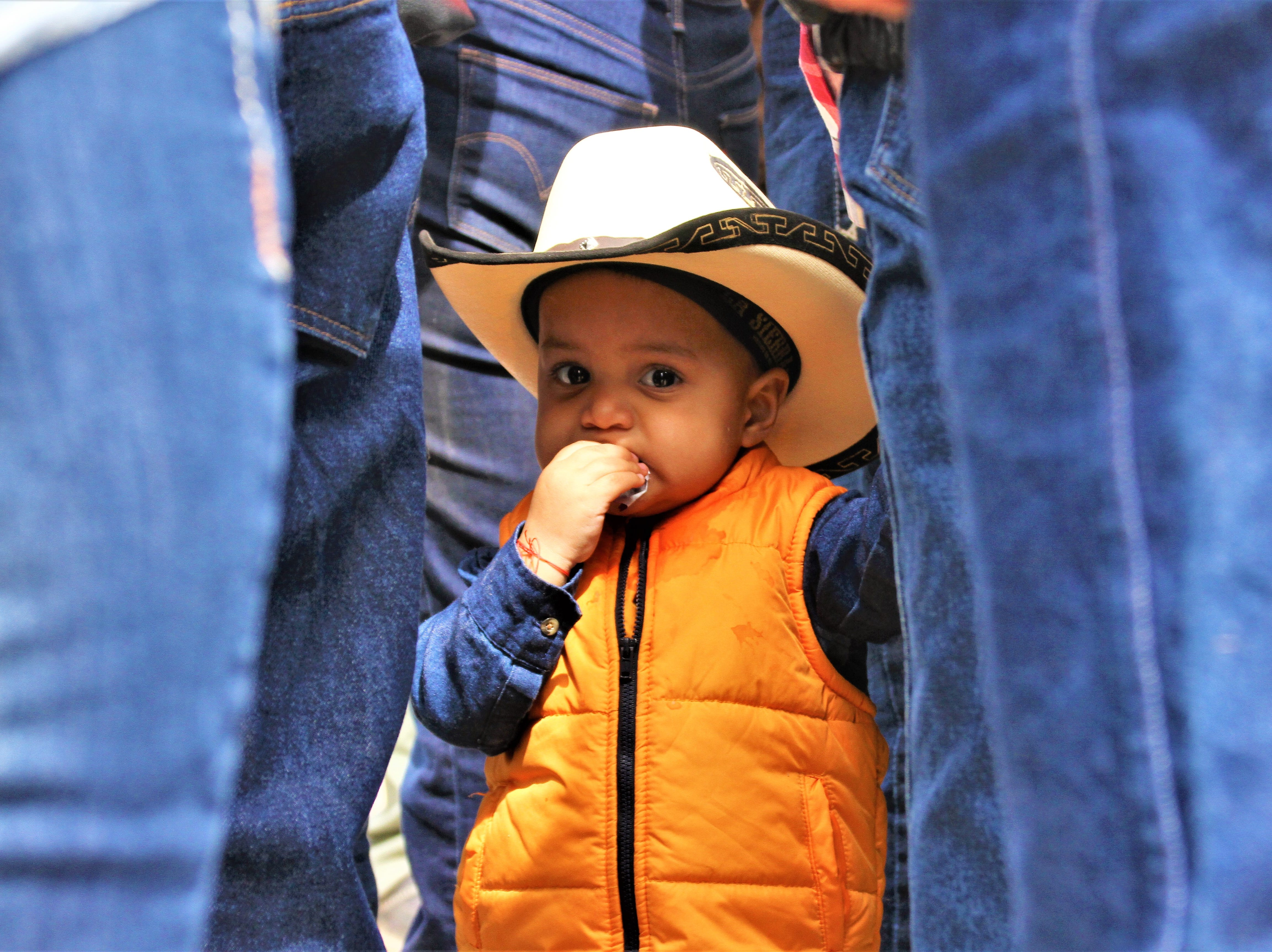 Between rows of legs - whose owners watched the fiesta performances - stood 1-year old Eiden Gracia.