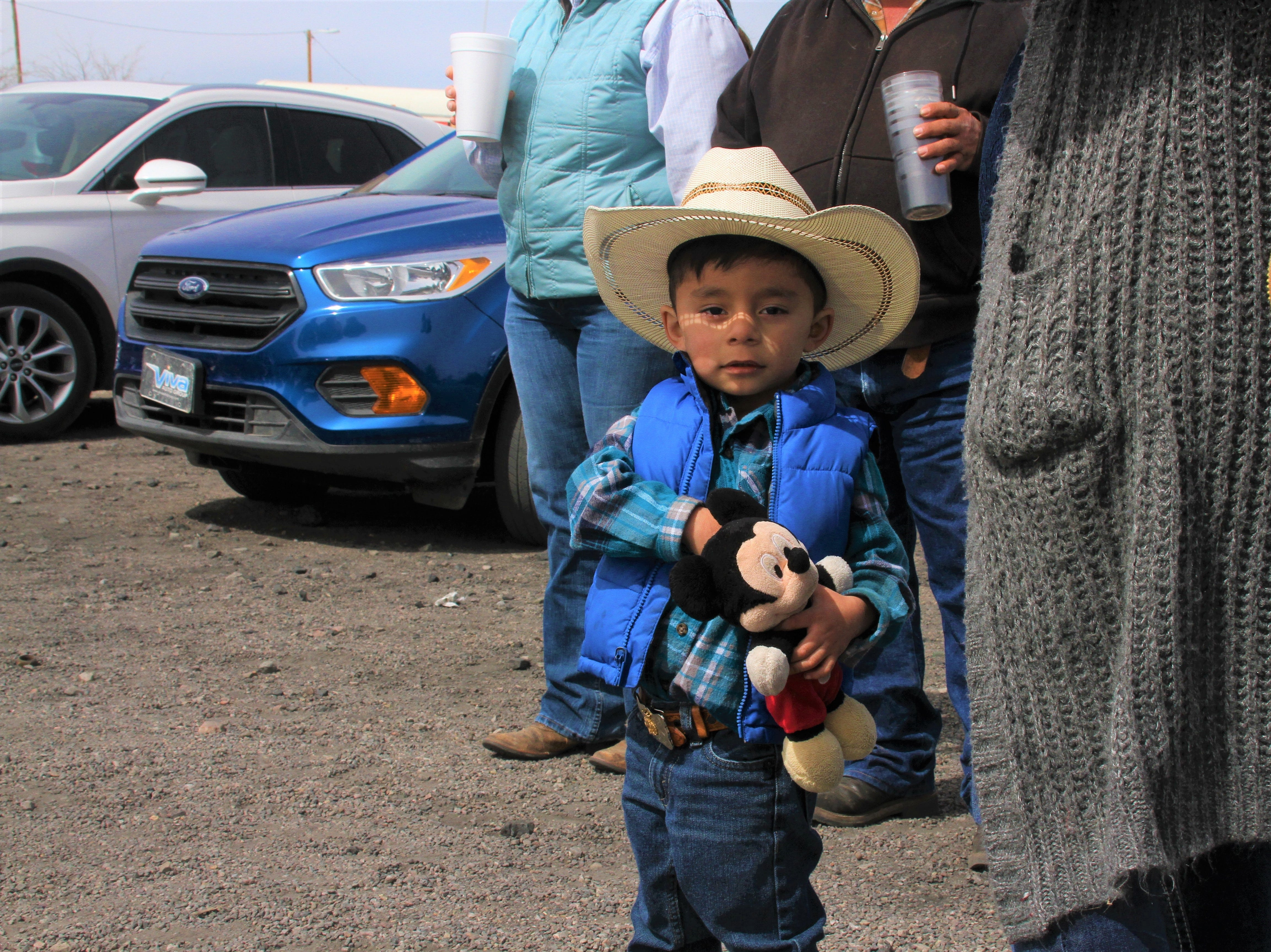 Three-year-old Gael Valdez and his family watch as the binational cavalry settles into Columbus.