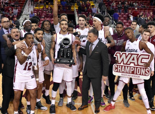 The New Mexico State University men's team celebrates becoming the 2019 regular season Western Athletic Conference champions after a win Saturday, March 9, 2019, at the Pan American Center.