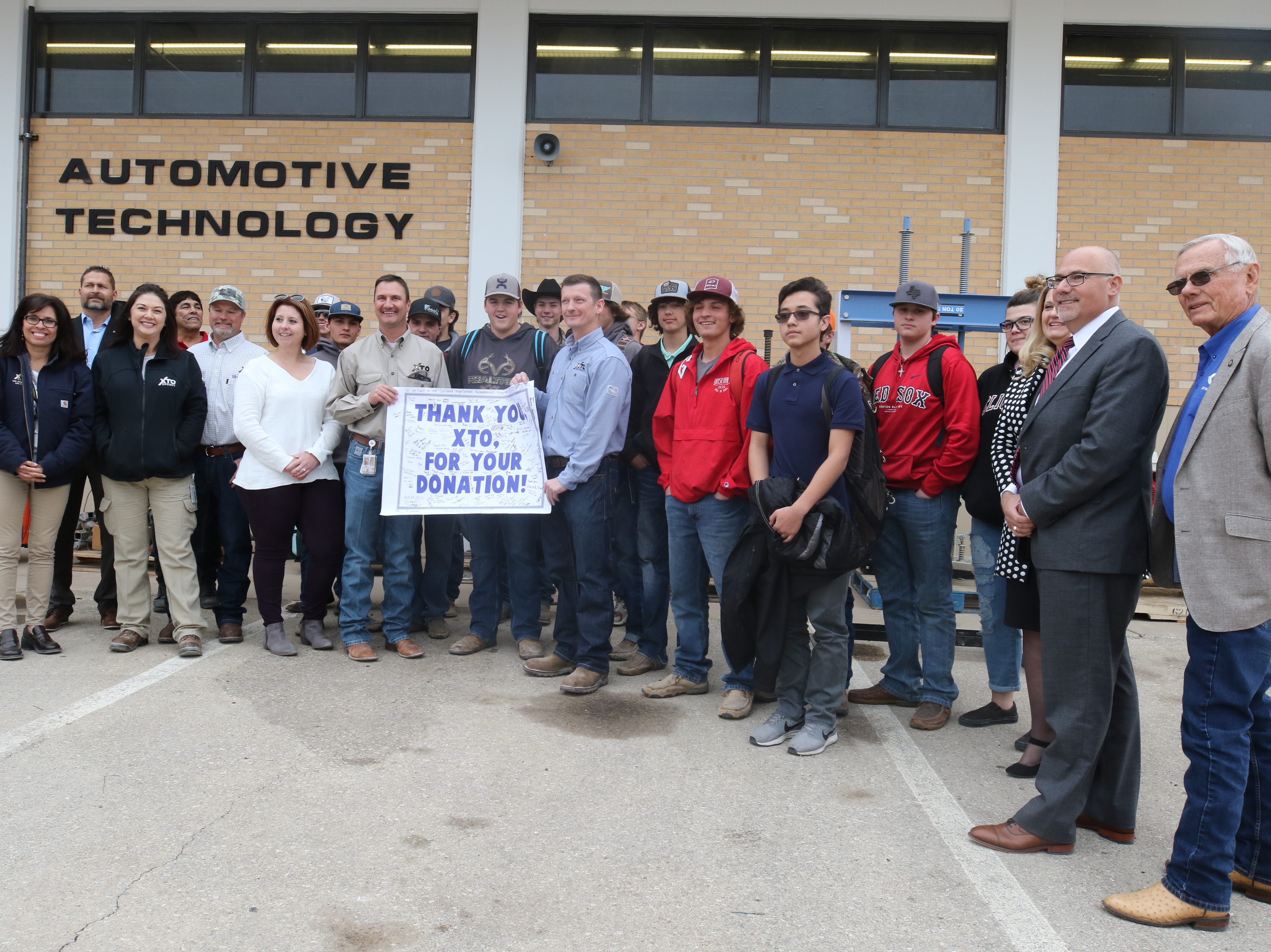 Officials from XTO Energy are presented with a commemorative banner from automotive students and staff, March 11, 2019 at Carlsbad High School.