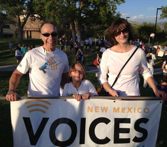 New Mexico Voices for Children Senior Policy Advisor Bill Jordan (left) helps carry the NM Voices' banner in a march for immigrant rights in Albuquerque.