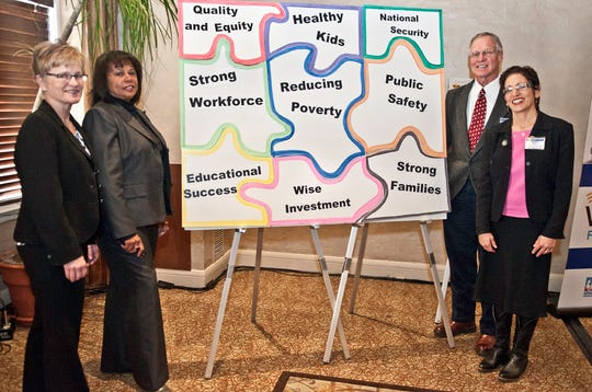 """Jessie Rasmussen (Buffett Early Childhood Fund, Nebraska), Diana Ragbeer (The Children's Trust, Florida), Duane Benson (Minnesota Early Learning Foundation), and Myra Segal (NMVC) pose with a large puzzle at our """"Transforming Education"""" convening. The puzzle represents the many links between early care and education and the quality of life for all."""