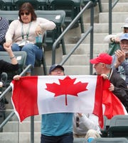 Fans of Milos Raonic of Canada wave a flag during a match against Marcos Giron of the U.S.A. on Stadium One at the 2019 BNP Paribas Open at Indian Wells Tennis Garden on March 11, 2019. Raonic won the fourth round match in thee sets 4-6, 6-4, 6-4.