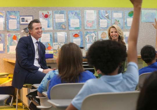 Gov. Gavin Newsom accompanied by his wife, Jennifer Siebel Newsom, take questions from sixth graders at the Washington Elementary School in Sacramento on Friday, March 1. California's first couple visited the school to celebrate Read Across America Day.