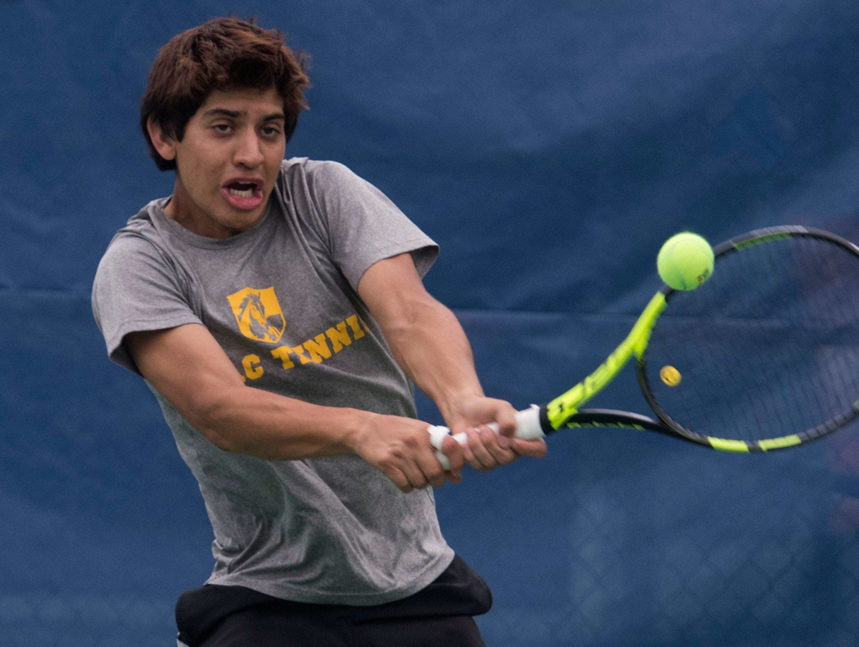 Juan Pino, from Abraham Baldwin Agricultural College, returns the serve from the Seward County Community College team during doubles play in the Western Gate Tennis Invitational tournament at UWF on Monday, March 11, 2019. Seward won the match 8-6.