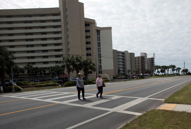Pedestrians dodge traffic on Perdido Key Drive on Friday. The Florida Department of Transportation and Escambia County are considering a road swap that would exchange 6.2 miles of Perdido Key Drive for 3.4 miles of Beulah Road.