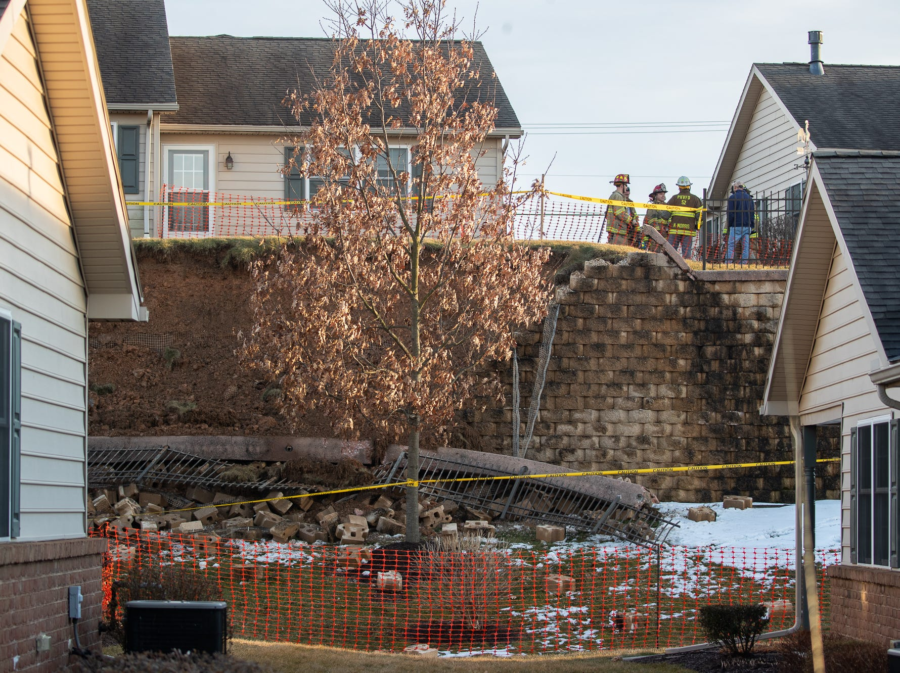 Emergency personnel work at the scene of a retaining wall collapse on the 1000 block of Bear Crossing, Sunday, March 10, 2019, in West Manheim Township. No one was injured in the collapse, which forced the evacuations of 26 housing units.