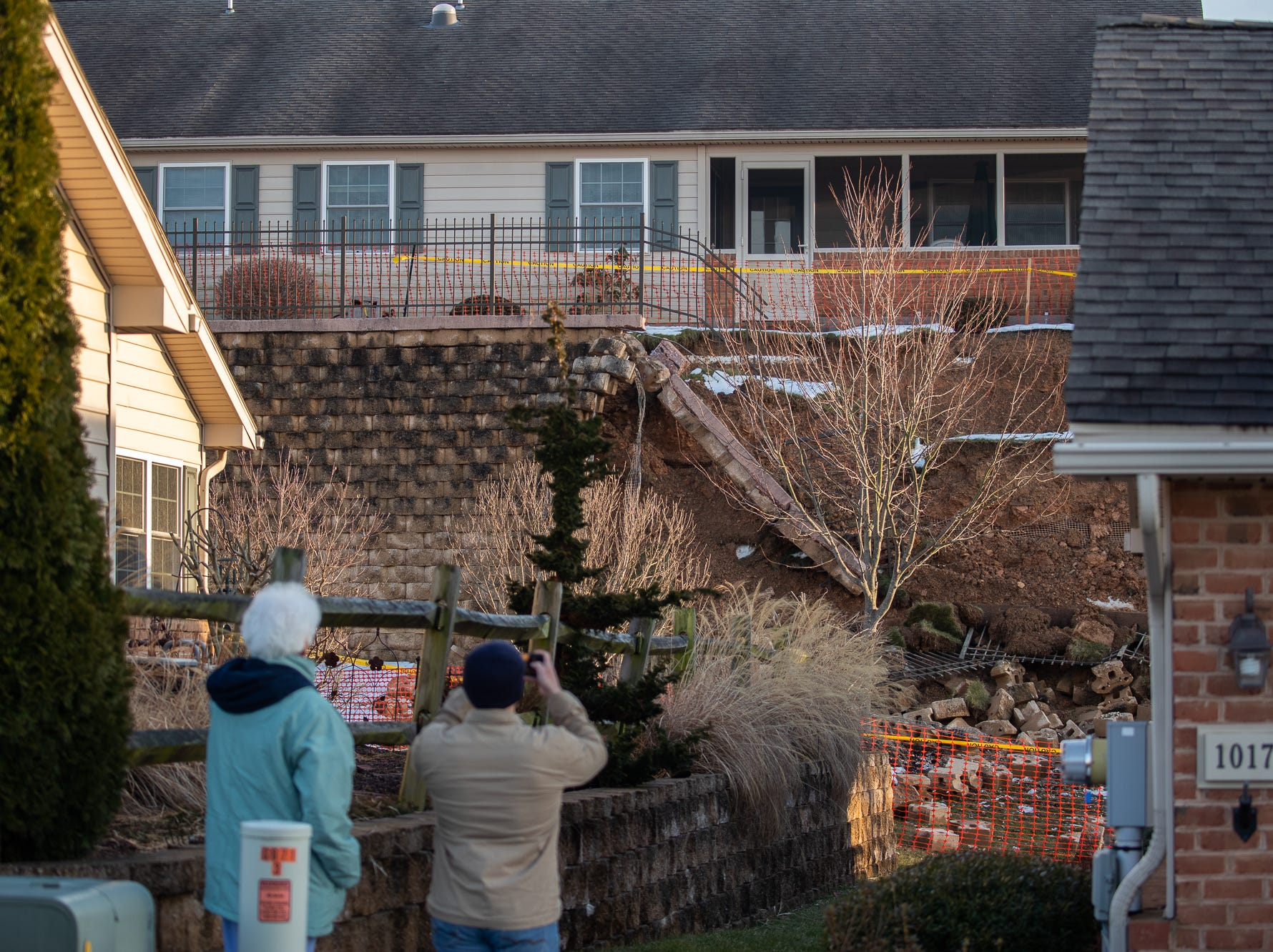 Onlookers take photos at the scene of a retaining wall collapse on the 1000 block of Bear Crossing, Sunday, March 10, 2019, in West Manheim Township. No one was injured in the collapse, which forced the evacuations of 26 housing units.