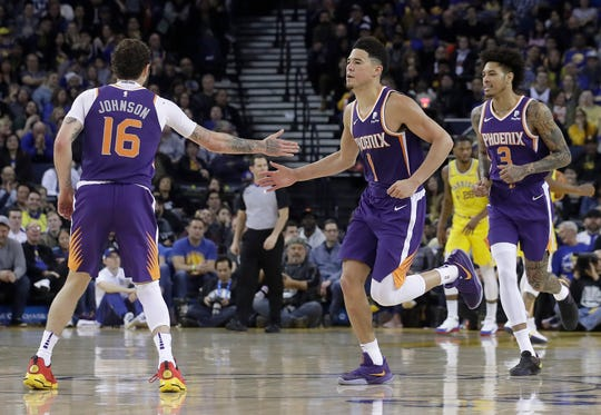 Phoenix Suns guard Devin Booker (1) celebrates with guard Tyler Johnson (16) and forward Kelly Oubre Jr. (3) during the second half of an NBA basketball game against the Golden State Warriors in Oakland, Calif., Sunday, March 10, 2019. (AP Photo/Jeff Chiu)