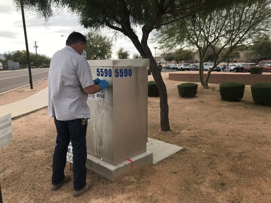 A Chandler Unified School District Employee removes the messages featuring swastikas from a transformer near Perry High School in Gilbert around 12:20 p.m. on March 11, 2019.