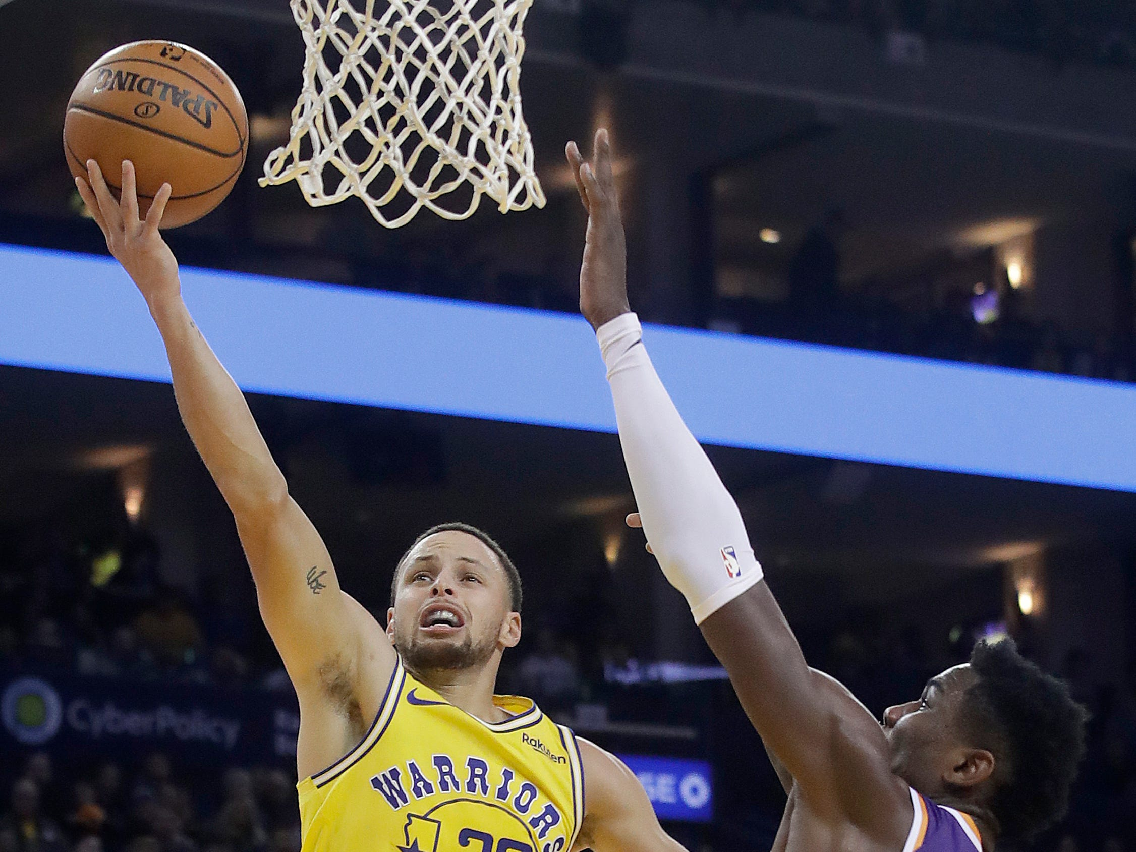 Golden State Warriors guard Stephen Curry, left, shoots against Phoenix Suns center Deandre Ayton, right, during the second half of an NBA basketball game in Oakland, Calif., Sunday, March 10, 2019. (AP Photo/Jeff Chiu)
