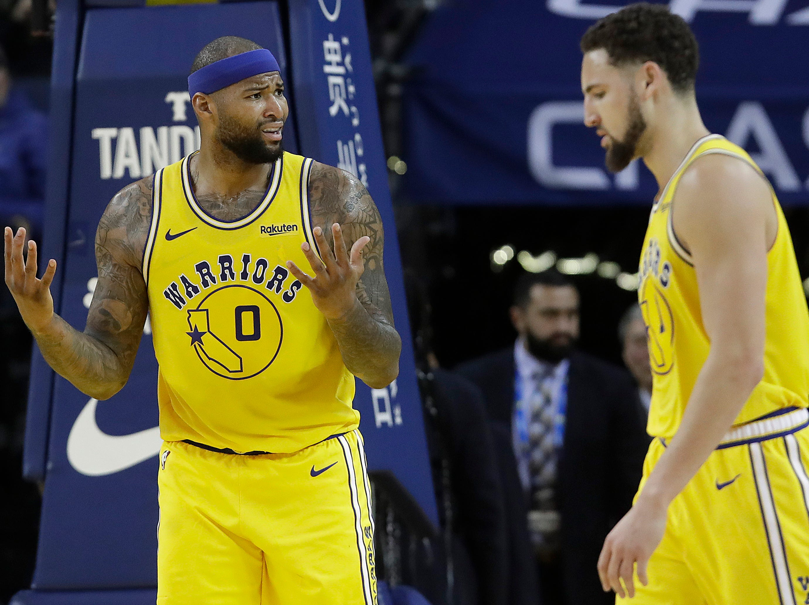 Golden State Warriors center DeMarcus Cousins, left, reacts to an official's call next to Klay Thompson during the second half of an NBA basketball game against the Phoenix Suns in Oakland, Calif., Sunday, March 10, 2019. (AP Photo/Jeff Chiu)