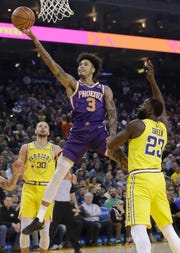 Phoenix Suns forward Kelly Oubre Jr. (3) shoots between Golden State Warriors guard Stephen Curry (30) and forward Draymond Green (23) during the first half of an NBA basketball game in Oakland, Calif., Sunday, March 10, 2019. (AP Photo/Jeff Chiu)